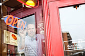 Male business owner adjusting open sign in diner window - Stock Image - DA4WGX