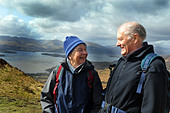 Active elderly people go hill walking in the Trossachs National Park, Scotland - Stock Image - BKW9PP