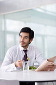 A man in a cafe or office canteen, reading a newspaper - Stock Image - B7MN68