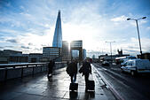 London, UK - 17 December 2014: businessmen with trolleys cross London Bridge as the sun shines behind buildings and The Shard - Stock Image - ECNYXD