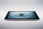Digital tablet with water drop on screen - Stock Image - D9DHE7