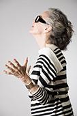 Portrait of senior woman, arms open, side view - Stock Image - E0B8A1