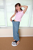 young woman happy to have lost weight - Stock Image - BJ7MH6