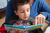Mother helps child to read - Stock Image - D72W4K