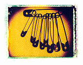 STEEL SAFETY PINS ON POLAROID IMAGE TRANSFER - Stock Image - ABH06P