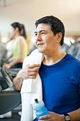 Older man toweling off in gym - Stock Image - CRKG0G