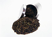Black tea falling out of open round tea caddy - Stock Image - B45F5N