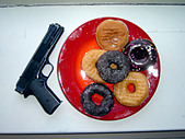 Still Life of a Red Plate With Six Donuts Near a Police Pistol - Stock Image - AT6AXY