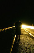 A dark portrait image of a man walking down a road at night © Paul Thomas Gooney - Stock Image - B2E6JG
