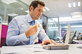 Businessman eating sushi in office - Stock Image - DTAKYC