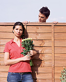 Man looking at woman over garden fence - Stock Image - A0WJKF
