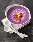 Cream of Vitelotte potato soup with crushed hazelnuts and flaked grisons meat - Stock Image - C8EFB8