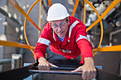 Worker climbing ladder at oil refinery - Stock Image - CRJ8RH