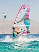 A windsurfer performing tricks on the red sea at the resort of Eilat in Israel. - Stock Image - C4HGCK