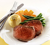 Two slices of roast beef with a dumpling and vegetables - Stock Image - AF55ER
