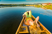Woman relaxes in a canoe on Six Mile Lake near Anchorage Alaska during Summer - Stock Image - BNN1A0