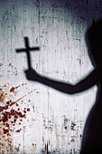 shadow of a person with a crucifix on a bloody white wall - Stock Image - D2FF5K
