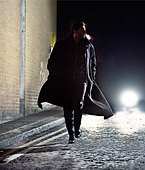 man in overcoat running down street at night - car lights behind - Stock Image - B7YGJ6