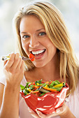 Young Woman Eating Fresh Salad - Stock Image - B7JCJ5