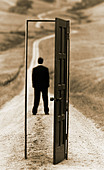 "conceptual photograph of executive man standing on country road framed with an ""open door"" - Stock Image - BR1Y8A"