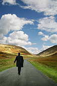 a man walking down an open road - Stock Image - A310BK