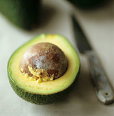 Half an avocado with stone - Stock Image - BJM546