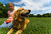 Young girl at park with pet Dog - Stock Image - CXN54N