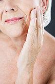 A senior woman touching her cheek - Stock Image - B7MHGB