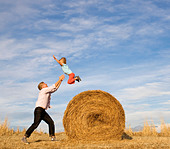 man catching boy jumping from hay bale - Stock Image - BH2R1D