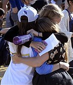epa04228931 People hug following a memorial event for the six UCSB students killed and 13 wounded in a shooting rampage in the college town of Isla Vista, at Harder Stadium at the University of California in Goleta, California, USA, 27 May 2014. The suspected gunman, 22-year-old student Elliot Rodger, killed six people and wounded 13 as he drove through the college town shooting as well as running over victims in his BMW car before he died from a self-inflicted wound. Over 18,000 people mainly students attended the memorial service.  EPA/MICHAEL NELSON - Stock Image - E1CHM6