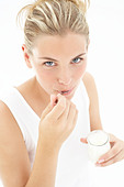 A young woman eating yogurt - Stock Image - ACKNMB
