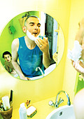 Two men in bathroom, one shaving, one in tub, reflection in mirror. - Stock Image - AWPY8E
