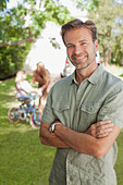 Portrait of smiling man with family in background - Stock Image - D2XJ6T