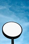 Circular White Sign on a Pole Against a Clear Blue Sky on a Sunny Day with Copy Space - Stock Image - AJXM8H