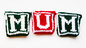 "Knitted woollen lettering spelling ""Mum"" - Stock Image - ED87C8"
