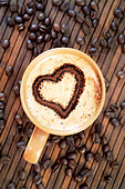 Cappuccino with heart decoration in milk foam & coffee beans - Stock Image - BJP9P4