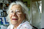 Portrait of a happy smiling British pensioner at her home in London UK - Stock Image - A5P5BP