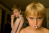 Young boys pretend to smoke gum cigarettes. - Stock Image - CY1D4Y