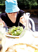 young woman eating salad for lunch outdoors - Stock Image - AAY59D