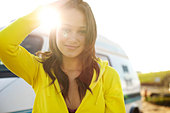 Female in her early 20's wearing a bright yellow hoodie poses in front of a vintage vehicle. - Stock Image - BKY37W