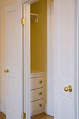 Open doors to empty closet with dresser - Stock Image - BGHCXE