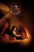 The magical treasure chest Five year old girl sits on bed with canopy and opens a box - Stock Image - B34K5A