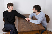 Young gay couple holding hands across table - Stock Image - A320HT