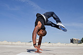 Man doing handstand on rooftop - Stock Image - CW04MX