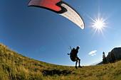 Paraglider taking off, backlit, wide-angle shot, Brauneck, Upper Bavaria, Germany, Europe - Stock Image - B77PYH
