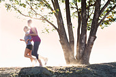 Women running together on dirt path - Stock Image - CR16E1