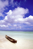 Dugout canoe on white sand beach in the Mallucu Islands of eastern Indonesia - Stock Image - A5E113