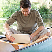 Young man sitting in a boat working on a laptop - Stock Image - A7GWXX