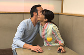 young man and women exchanging welcome kiss in cafe - Stock Image - A3KWRE