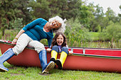 Grandmother and granddaughter sitting on canoe - Stock Image - CT7CJN
